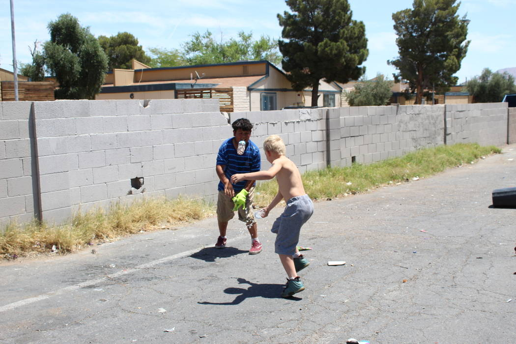 Theajion Grigsby, 8, and Martin Zamora, 13, have an impromptu water fight on Saturday, May 19 after cleaning up trash in an alley behind NAPA Auto Parts, 3274 Civic Center Drive, in North Las Vega ...