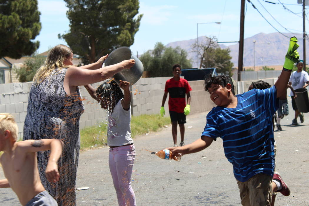 Members of the Youth Helping Hands have an impromptu water fight on Saturday, May 19 after cleaning up trash in an alley behind NAPA Auto Parts, 3274 Civic Center Drive, in North Las Vegas. (Max M ...