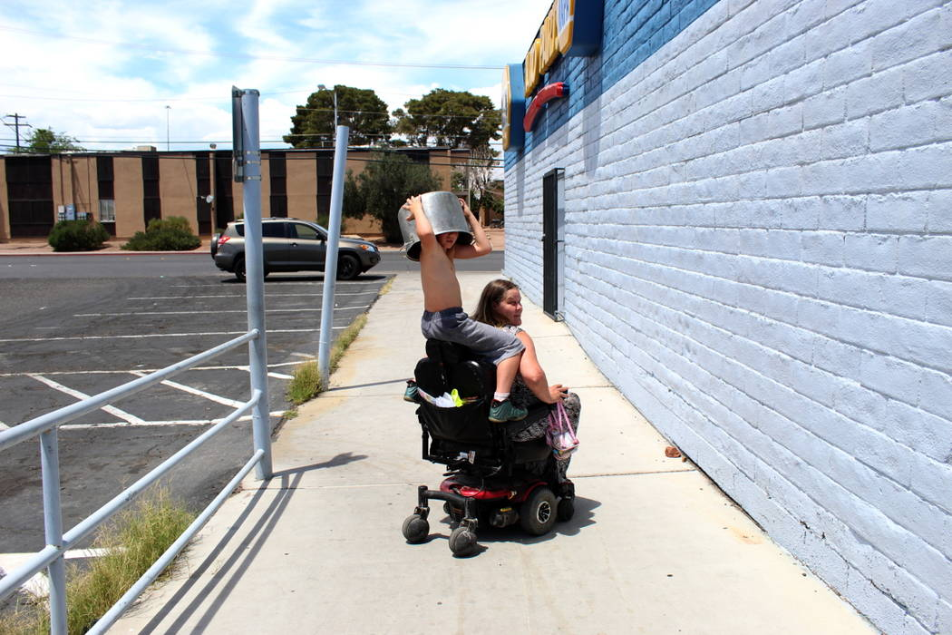 Theajion Grigsby, 8, hitches a ride on the back of Katt Smith's wheelchair as they return home on Saturday, May 19 after cleaning up trash in an alley behind NAPA Auto Parts, 3274 Civic Center Dri ...