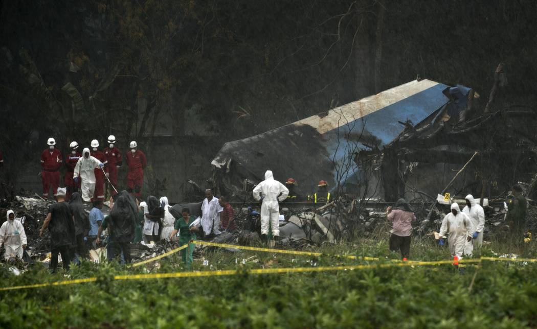 Rescue teams search through the wreckage site of a Boeing 737 that plummeted into a cassava field with more than 100 passengers on board, in Havana, Cuba, Friday, May 18, 2018. The Cuban airliner ...