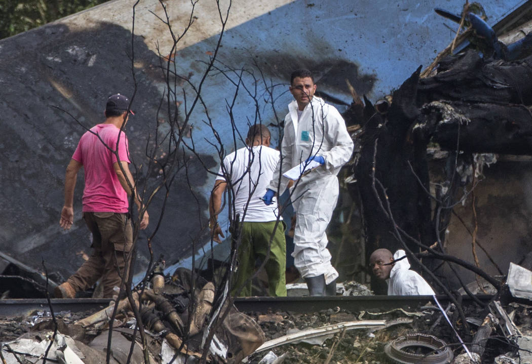 Forensic investigators and Ministry of Interior officers sift through the remains of a Boeing 737 that plummeted into a yuca field with more than 100 passengers on board, in Havana, Cuba, Friday, ...