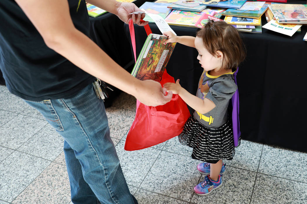 Emery Kountapanya, 3, gives her dad Brandon a book she picked out during the Reading Rangers Summer Reading Program at Boulevard Mall in Las Vegas on Saturday, May 19, 2018. Students were given th ...