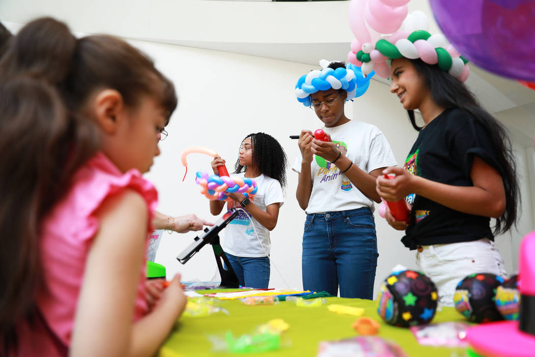 From left, Reyna Burch, 17, Mya Lofton, 19, and Susan Garcia, 19, make balloon animals for students during the Reading Rangers Summer Reading Program at Boulevard Mall in Las Vegas on Saturday, Ma ...