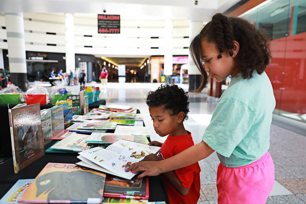Lynnea Lamb, 11, helps her brother Deon, 5, read a book during the Reading Rangers Summer Reading Program at Boulevard Mall in Las Vegas on Saturday, May 19, 2018. Students were given the opportun ...