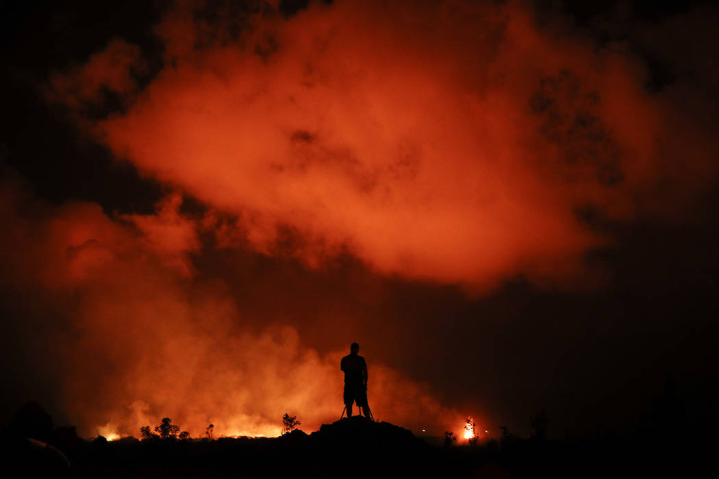 Peter Vance, 24, photographs lava erupting in the Leilani Estates subdivision near Pahoa, Hawaii Friday, May 18, 2018. Hawaii residents covered their faces with masks after a volcano menacing the ...