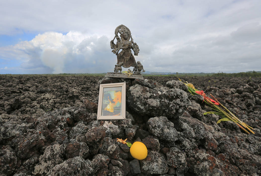 Offerings to Pele the Fire Goddess are left along Kapoho Road near Leilani Estates, Hawaii, where an ash plume from the ongoing Kilauea eruptions is visible, on Saturday, May 19, 2018. Brett LeBla ...