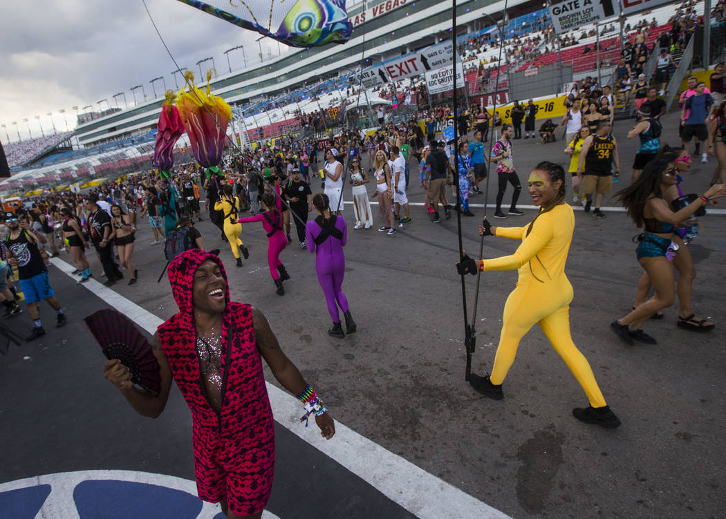 Zarkell Small of Florida, left, watches costumed performers pass by while dancing at the Cosmic Meadow stage during the second day of the Electric Daisy Carnival at the Las Vegas Motor Speedway in ...