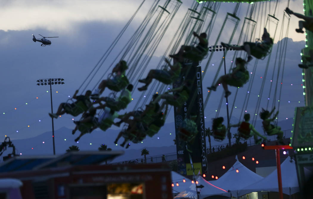 A helicopter departs as attendees enjoy a carnival ride during the second day of the Electric Daisy Carnival at the Las Vegas Motor Speedway in Las Vegas on Saturday, May 19, 2018. Chase Stevens L ...