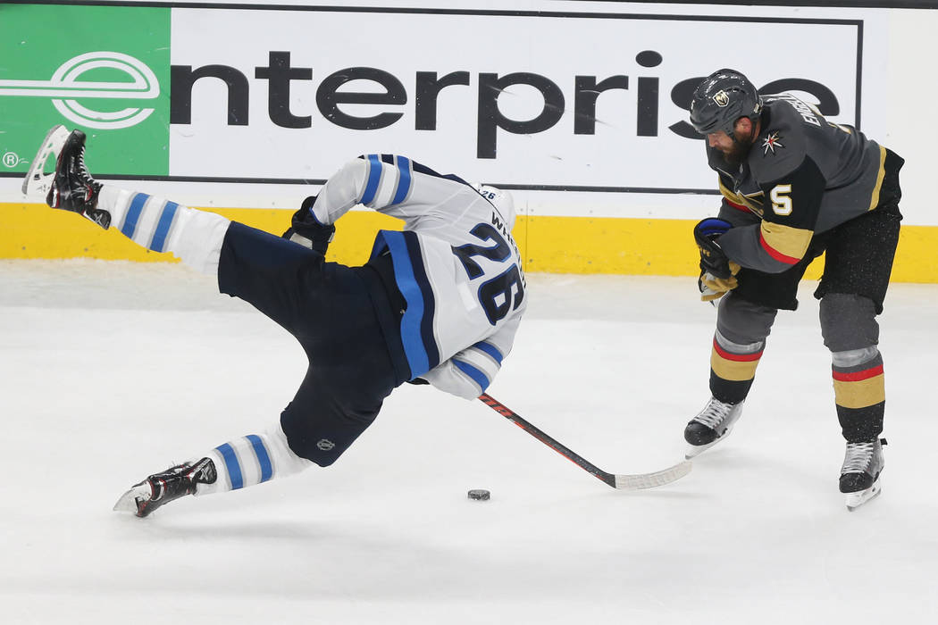 Winnipeg Jets right wing Blake Wheeler (26) takes a fall against Vegas Golden Knights defenseman Deryk Engelland (5) during the third period in Game 4 of the Western Conference Final at T-Mobile A ...
