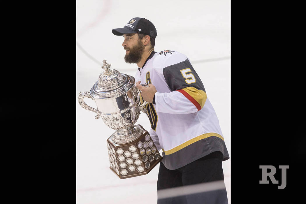 Golden Knights defenseman Deryk Engelland (5) holds the Clarence Campbell Bowl trophy after Las Vegas beat the Winnipeg Jets 2-1 to advance to the Stanley Cup Finals on Sunday, May 20, 2018, at Be ...
