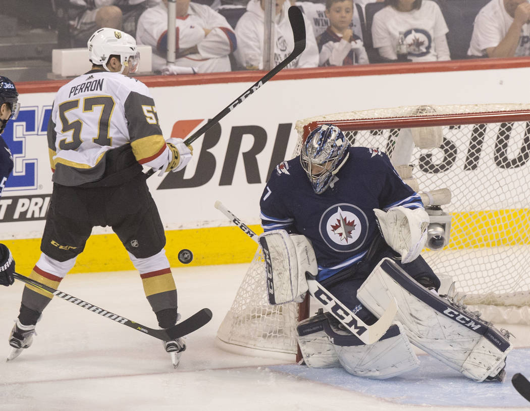 Jets goaltender Connor Hellebuyck (37) makes a save on Golden Knights left wing David Perron (57) in the first period during game five of the NHL Western Conference Finals on Sunday, May 20, 2018, ...