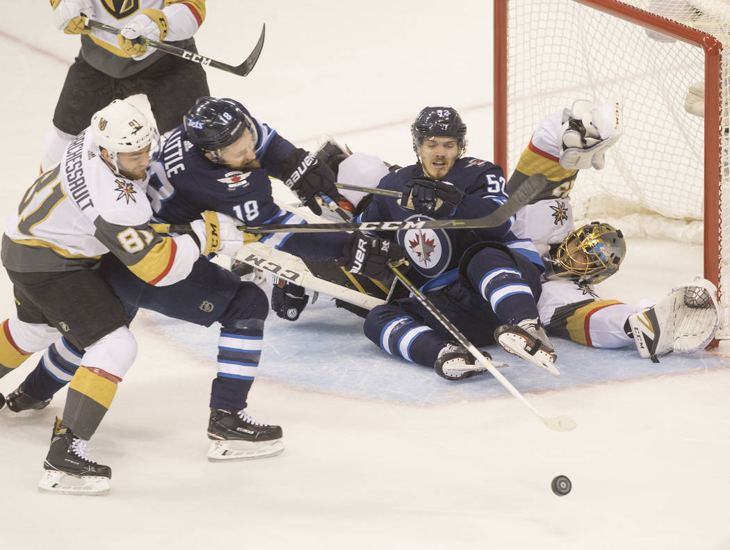 Golden Knights goaltender Marc-Andre Fleury (29) collides with Jets center Jack Roslovic (52) while making a save in the first period during game five of the NHL Western Conference Finals on Sunda ...