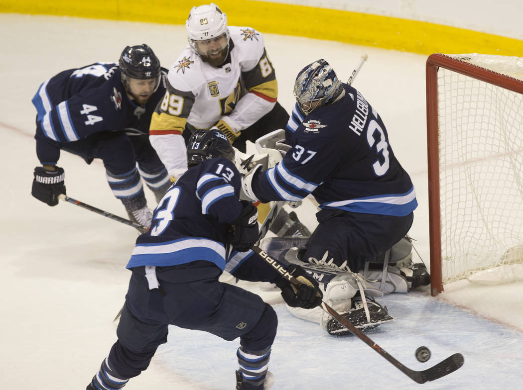 Jets goaltender Connor Hellebuyck (37) makes a save on Golden Knights right wing Alex Tuch (89) in the second period during game five of the NHL Western Conference Finals on Sunday, May 20, 2018, ...