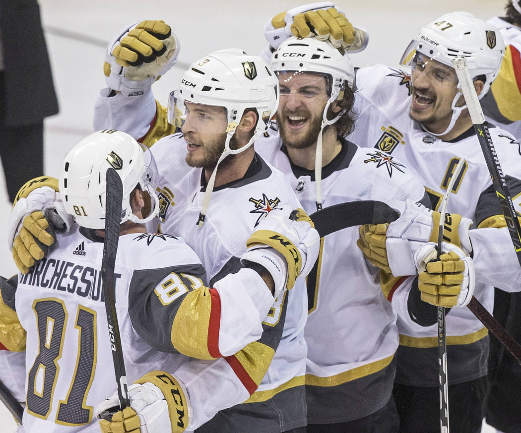 Golden Knights center Jonathan Marchessault (81) hugs teammates Brayden McNabb (3), Colin Miller (6) and Luca Sbisa (47) after beating the Winnipeg Jets 2-1 to advance to the Stanley Cup Finals on ...