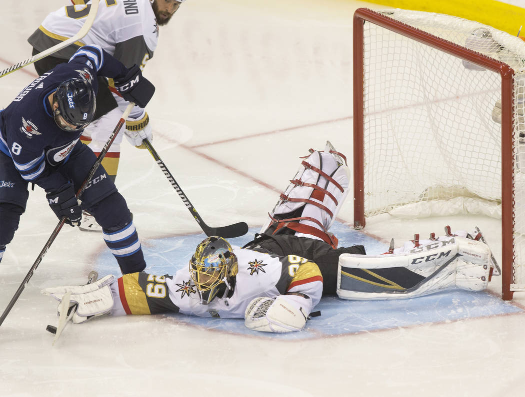 Golden Knights goaltender Marc-Andre Fleury (29) makes a save against Jets defenseman Jacob Trouba (8) in the third period during game five of the NHL Western Conference Finals on Sunday, May 20, ...