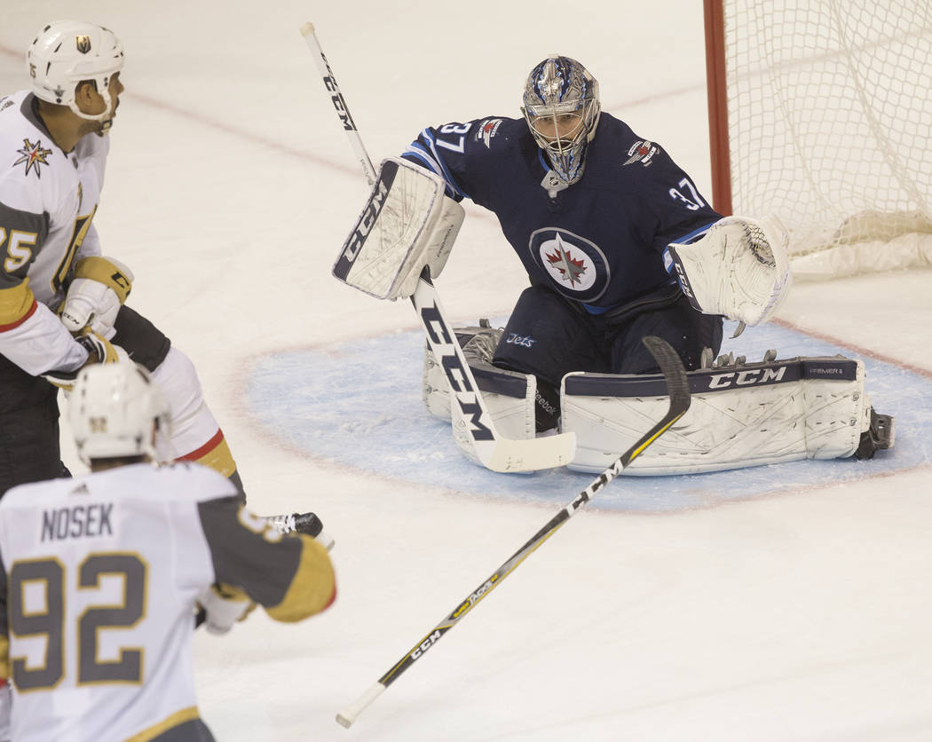 Jets goaltender Connor Hellebuyck (37) avoids a stick from Golden Knights center Tomas Nosek (92) in the second period during game five of the NHL Western Conference Finals on Sunday, May 20, 2018 ...
