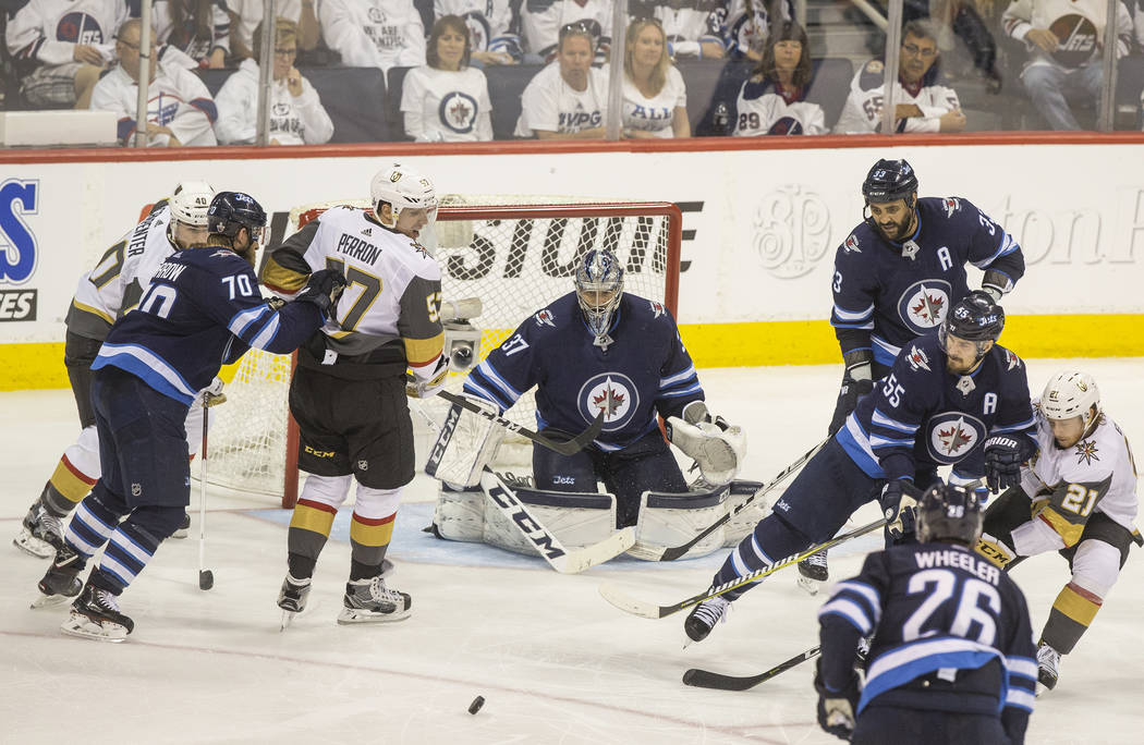 Jets goaltender Connor Hellebuyck (37) makes a save against Golden Knights left wing David Perron (57) in the third period during game five of the NHL Western Conference Finals on Sunday, May 20, ...