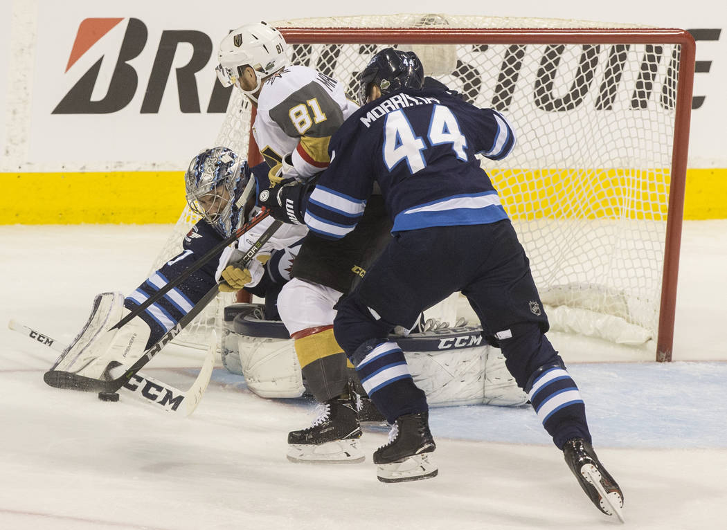 Jets goaltender Connor Hellebuyck (37) makes a save against Golden Knights center Jonathan Marchessault (81) with the help of Jets defenseman Josh Morrissey (44) in the third period during game ...
