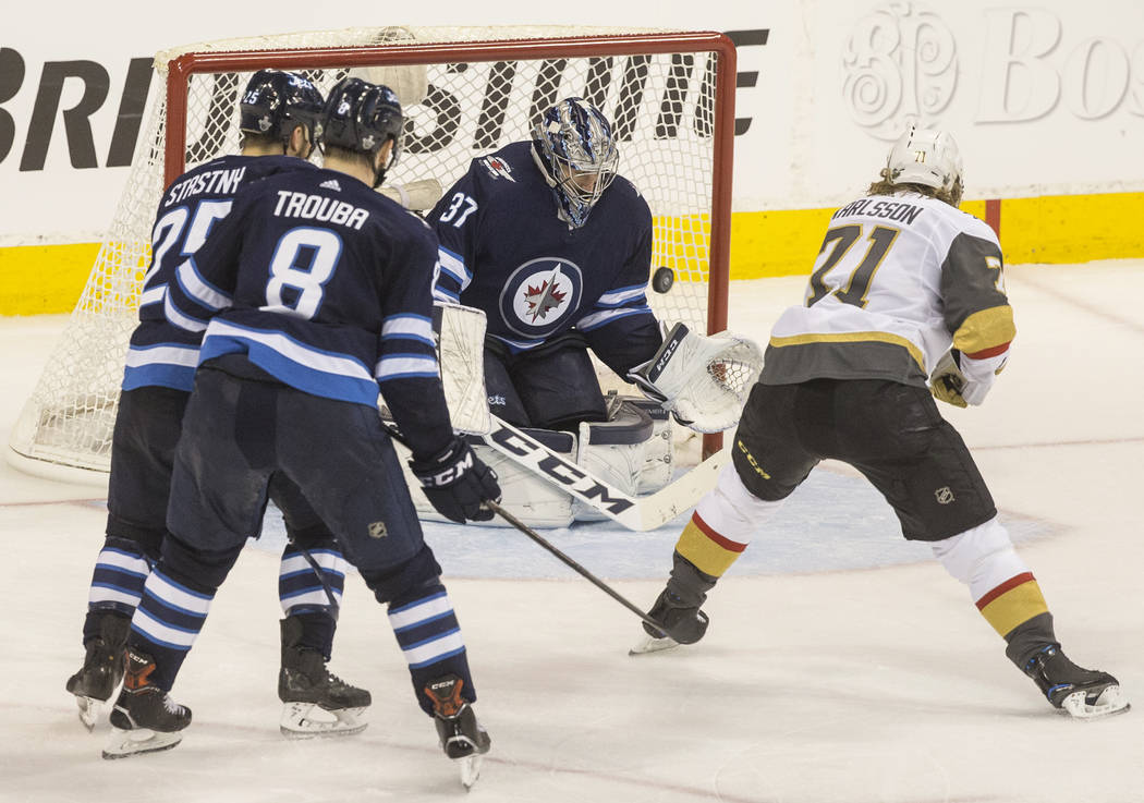 Jets goaltender Connor Hellebuyck (37) makes a save against Golden Knights center William Karlsson (71) in the third period during game five of the NHL Western Conference Finals on Sunday, May 20, ...
