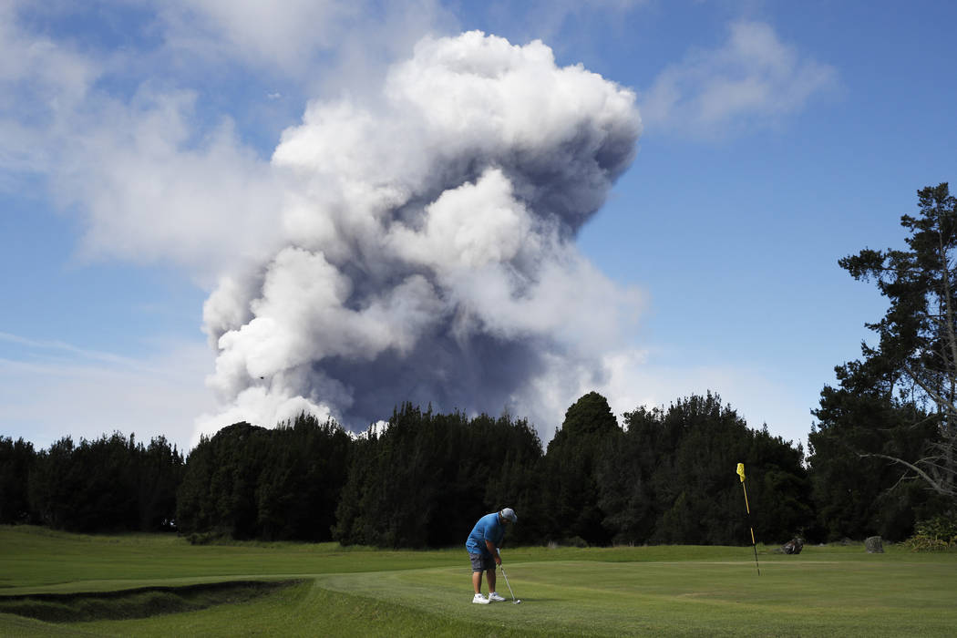 Doug Ralston plays golf in Volcano, Hawaii as a huge ash plume rises from the summit of Kiluaea volcano Monday, May 21, 2018. Kilauea has burned some 40 structures, including two dozen homes, sinc ...