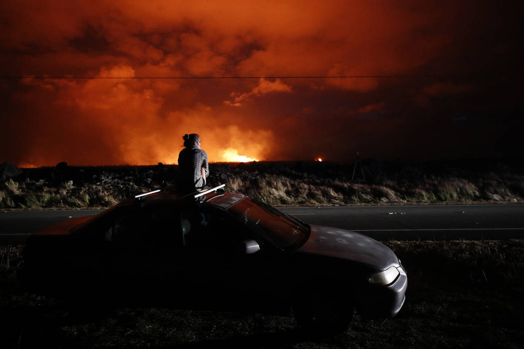 FILE - In this May 19, 2018 file photo, Brittany Kimball watches as lava erupts from a fissure near Pahoa, Hawaii. White plumes of acid and extremely fine shards of glass billowed into the sky ove ...