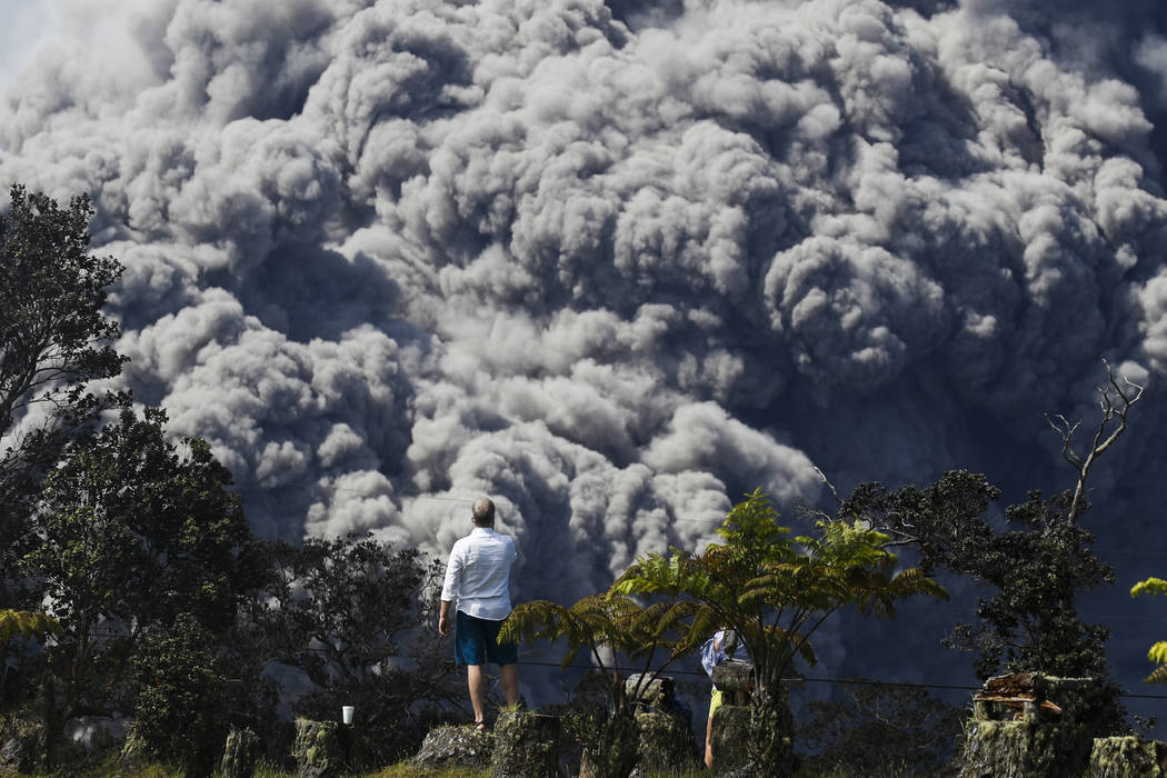 Jack Jones, visiting from Madison, Wis., takes pictures at a country club in Volcano, Hawaii as a huge ash plume rises from the summit of Kiluaea volcano Monday, May 21, 2018. Kilauea has burned s ...