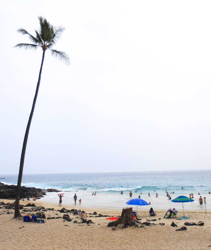 Beachgoers enjoy a day in the sand and surf at Magic Sands Beach Park south of Kona, Hawaii, on Monday, May 21, 2018. Although the affected area of the ongoing eruptions is small, some hotels have ...