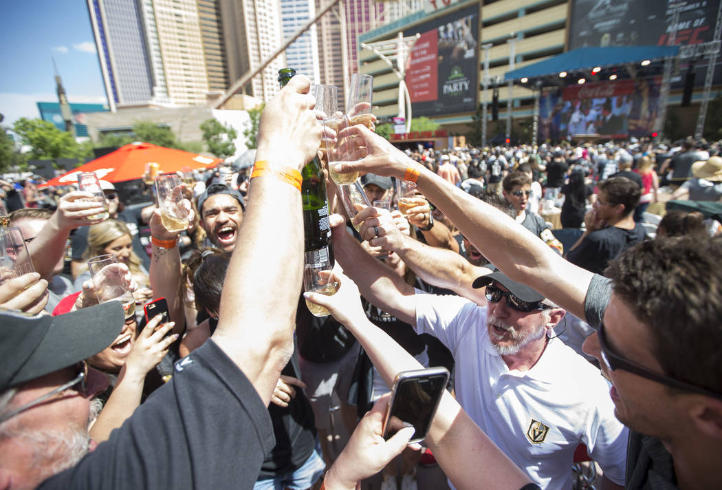 Golden Knights fans celebrate with a champagne toast after the Knights defeated the Winnipeg Jets 2-1 during a watch party for Game 5 of the Western Conference Finals at Toshiba Plaza in Las Vegas ...