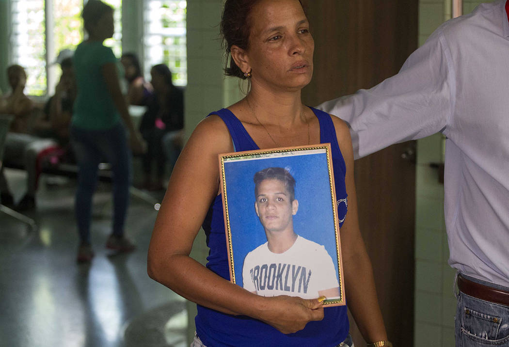 Mairy Charchabal holds a picture of her son Daniel Terrero Charchabal, 22, who was killed in Cuba's worst aviation disaster, at the morgue where she waits for the identification of the bodies in H ...