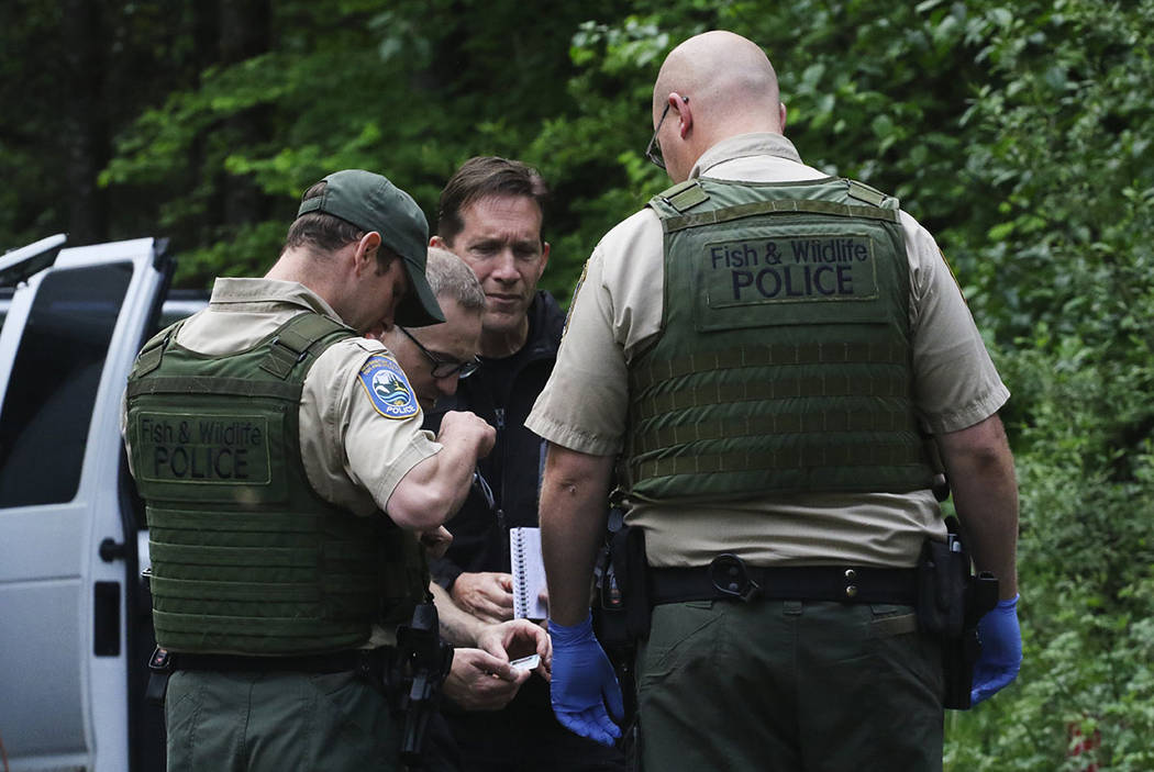 Washington State Fish and Wildlife Police confer with an individual from the King County Medical Examiner's and a King County Sheriff's deputy on a remote gravel road above Snoqualmie, WA., follow ...