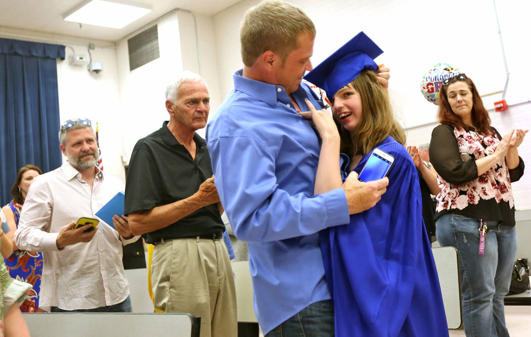 Sydney Goecke hugs her dad Jason Goecke on her way down the aisle at Helen J. Stewart School in Las Vegas, Wednesday, May 16, 2018. The special needs school hosted a graduation ceremony for studen ...