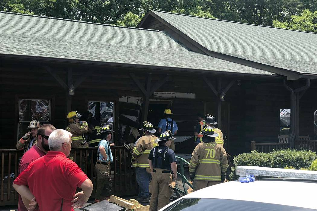 Authorities work the scene of a restaurant where police say a man intentionally rammed a vehicle into the steak and seafood eatery shortly after midday Sunday, May 20, 2018, in Bessemer City, N.C. ...