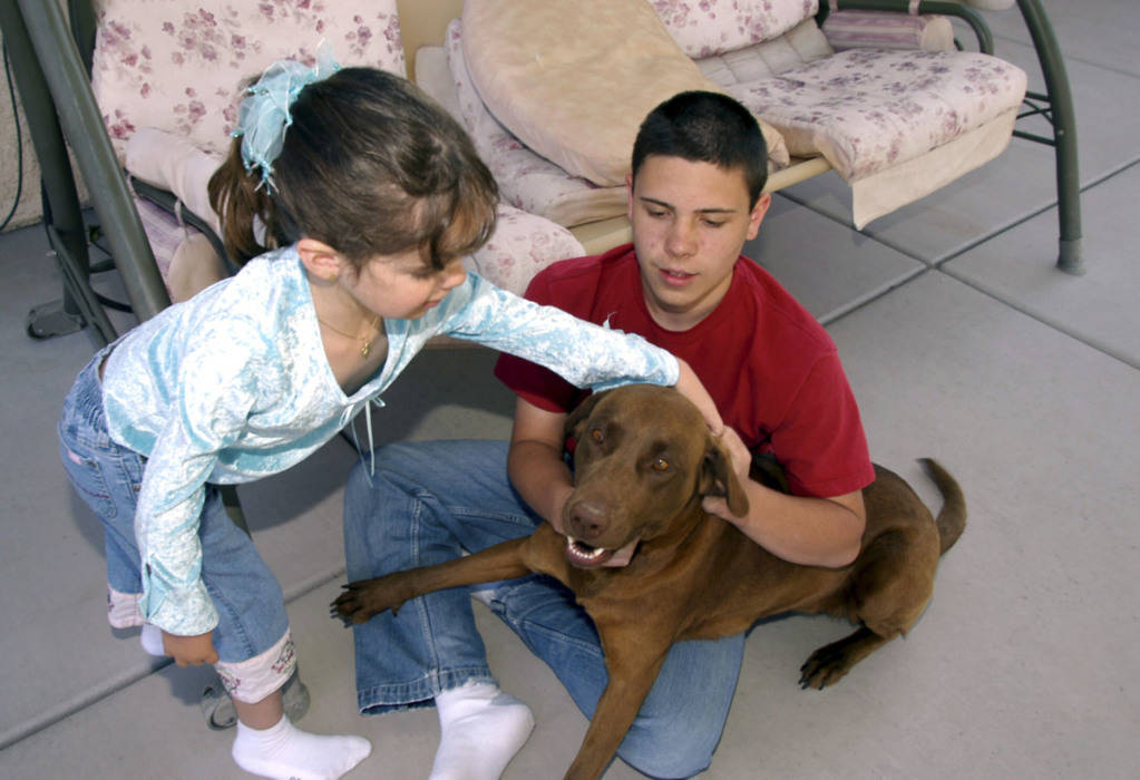 CN/VIEW--Seven year old Jessica Lindley pets the family dog, Cleo as her brother, Rayn holds the canine in their Las Vegas backyard, Thursday, 4/19/07. Jessica has taken 22 flights on Miracle Flig ...