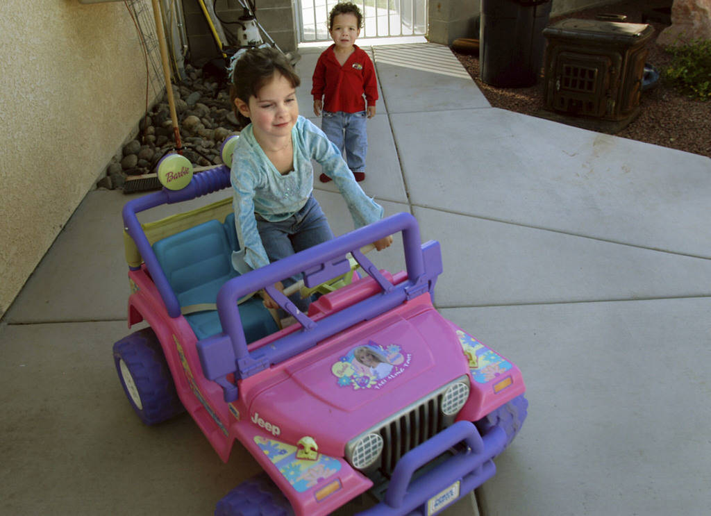 CN/VIEW--Seven year old Jessica Lindley drives her Jeep as her 2 year old brother, Carson watches in their Las Vegas backyard, Thursday, 4_19_07. Jessica has taken 22 flights on Miracle Flight for ...