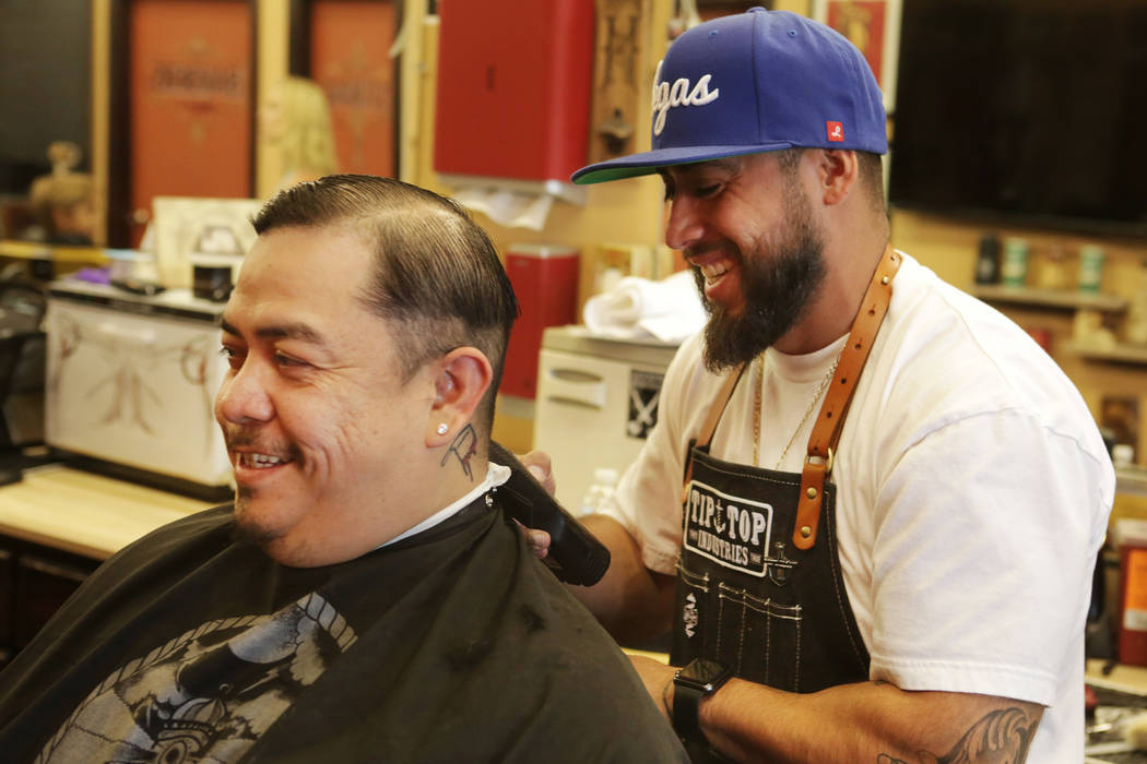 """Fernando Guzman, left, of Las Vegas chuckles with Moises """"Moy The Barber"""" Alvarez, owner of the Goodtimes Barber Shop & Shave Parlor on Sahara as he begins a Golden Knights hairc ..."""