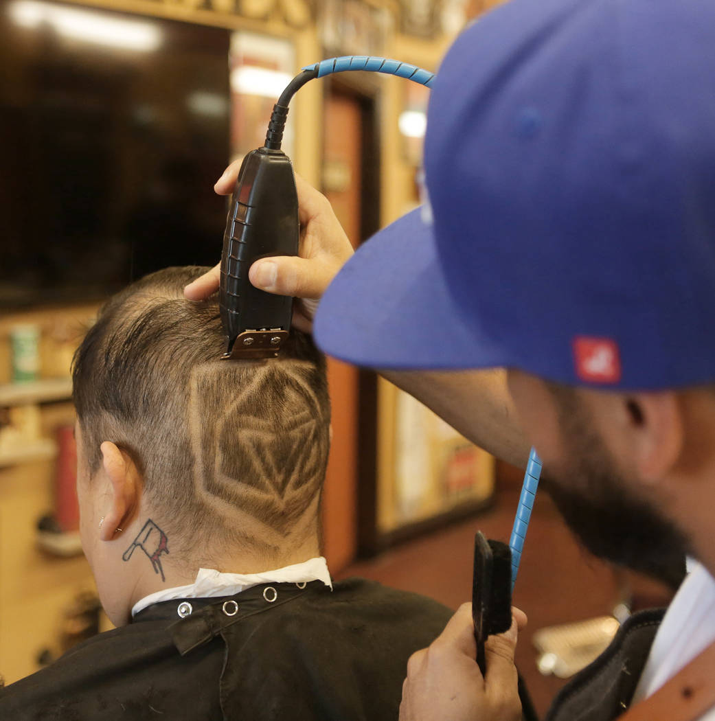 "Fernando Guzman, left, of Las Vegas gets a Golden Knights logo shaved on the back of his head by Moises ""Moy The Barber"" Alvarez, owner of the Goodtimes Barber Shop & Shave Parlo ..."