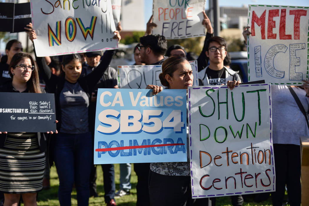 FILE - In this March 27, 2018, file photo, a group of sanctuary state supporters gather outside the Orange County Board of Supervisors meeting in Santa Ana, Calif., as they prepare to discuss join ...
