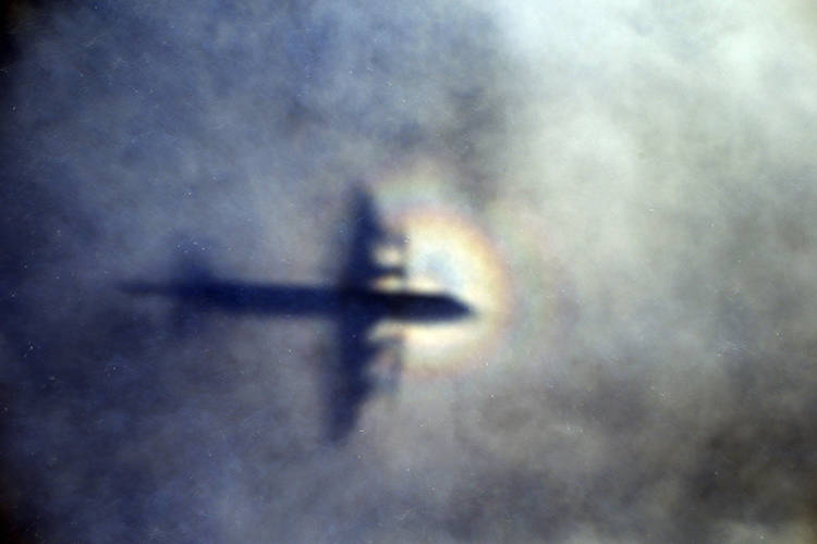 In this March 31, 2014 file photo, the shadow of a Royal New Zealand Air Force P3 Orion is seen on low level cloud while the aircraft searches for missing Malaysia Airlines Flight MH370 in the sou ...