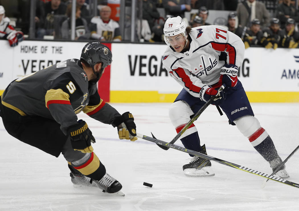 Washington Capitals right wing T.J. Oshie (77) tries to move the puck past Vegas Golden Knights defenseman Deryk Engelland during the second period of an NHL hockey game Saturday, Dec. 23, 2017, i ...