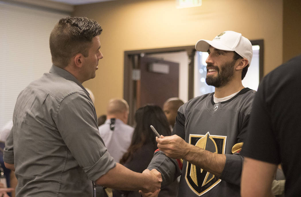 Metro detective Justin Roth, left, shakes hands with Vegas Golden Knights defenseman Jason Garrison (7) during a team appearance to show support for police officers at the department headquarters ...