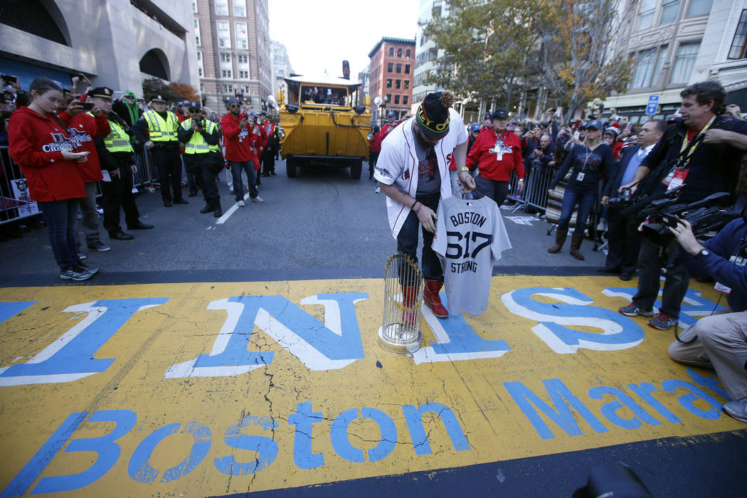 Boston Red Sox's Jonny Gomes places the championship trophy and a Red Sox baseball jersey at the Boston Marathon Finish Line during a pause in their World Series victory rolling rally in Boston, S ...