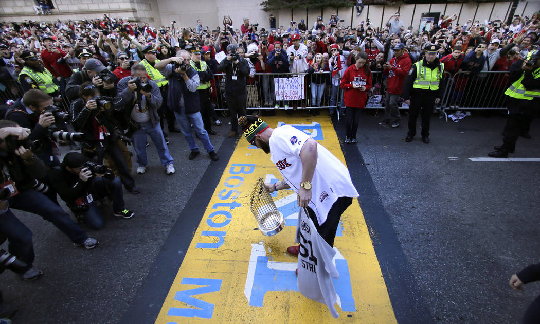 Boston Red Sox's Jonny Gomes puts the 2013 World Series trophy and a team jersey on the finish line of the Boston Marathon, in honor of those affected by the bombings, as they stopped the parade i ...