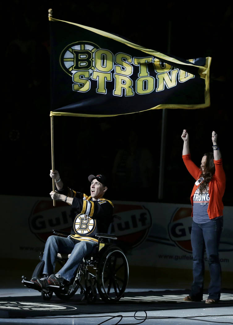 "Richard Donohue, the Massachusetts Bay Transportation Authority officer wounded during the shootout with the Boston Marathon bombing suspects, waves a ""Boston Strong"" banner as his wife, ..."