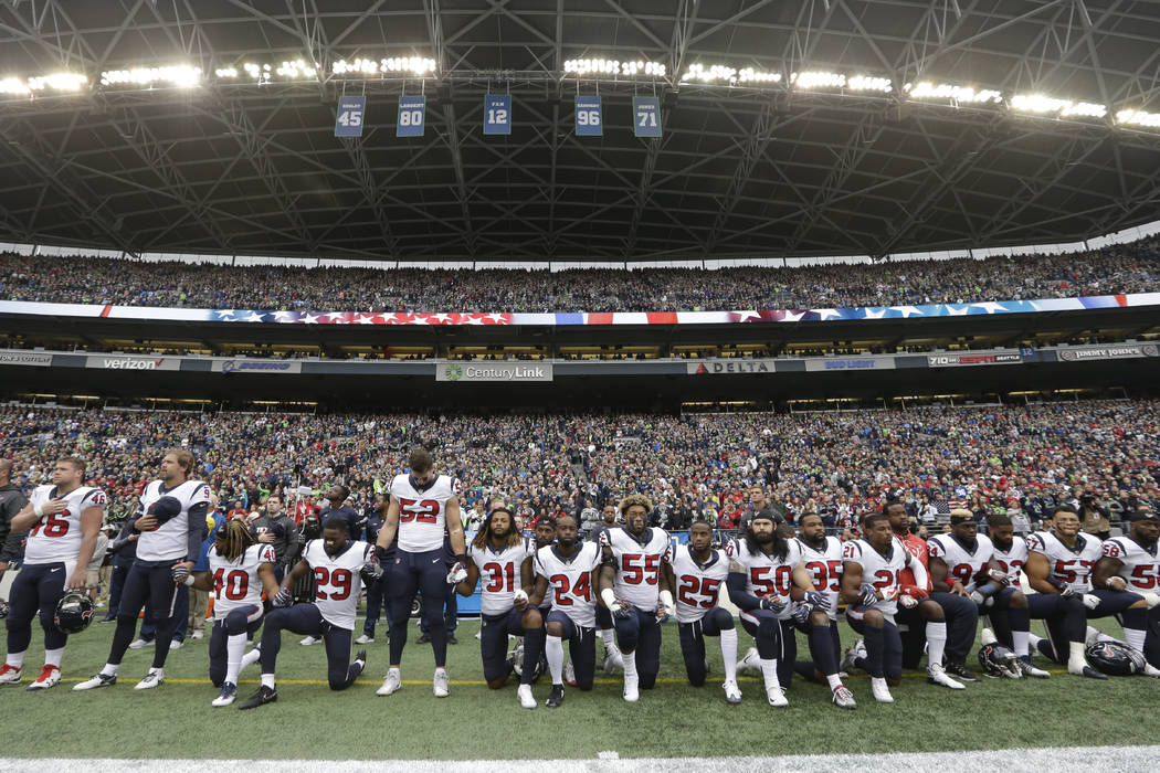 In this Oct. 29, 2017, file photo, Houston Texans players kneel and stand during the singing of the national anthem before an NFL football game against the Seattle Seahawks, in Seattle. (AP Photo/ ...