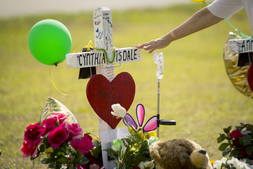 A woman gestures toward a cross honoring Santa Fe High School substitute teacher Cynthia Tisdale Tuesday, May 22, 2018, who was killed during a shooting at the school on Friday, in Santa Fe, Texas ...