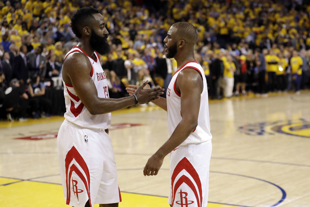 Houston Rockets' Chris Paul, right, shakes hands with teammate James Harden after a 95-92 win over the Golden State Warriors in Game 4 of the NBA basketball Western Conference Finals Tuesday, May ...