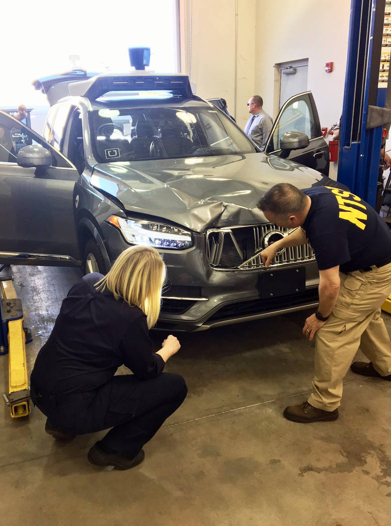 Investigators examine a driverless Uber SUV that fatally struck a woman in Tempe, Ariz. on March 20, 2018. (National Transportation Safety Board via AP, File)