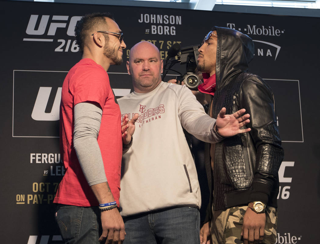 UFC lightweights Tony Ferguson, left, and Kevin Lee, right, staredown at the T-Mobile Arena as UFC president Dana White keeps them separated during UFC 216 media day in Las Vegas, Wednesday, Oct. ...