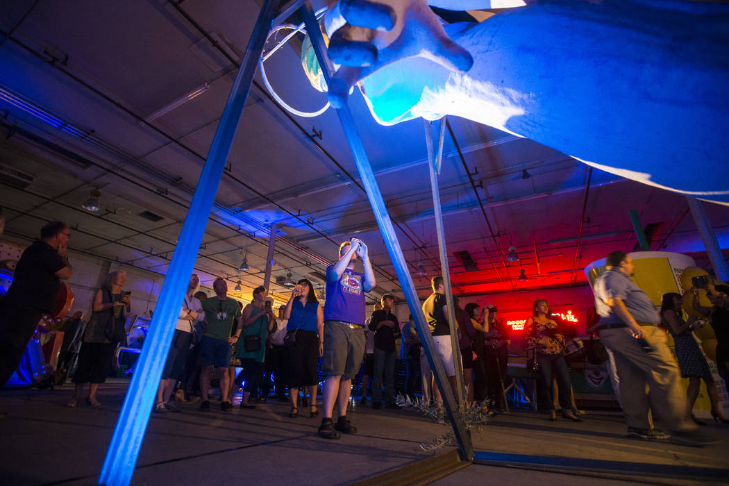 Visitors look at the Blue Angel statue, designed by Betty Willis, at the Neon Museum's Ne10 Studio in Las Vegas on Thursday, May 24, 2018. The statue came down from its perch in March of 2017 at t ...