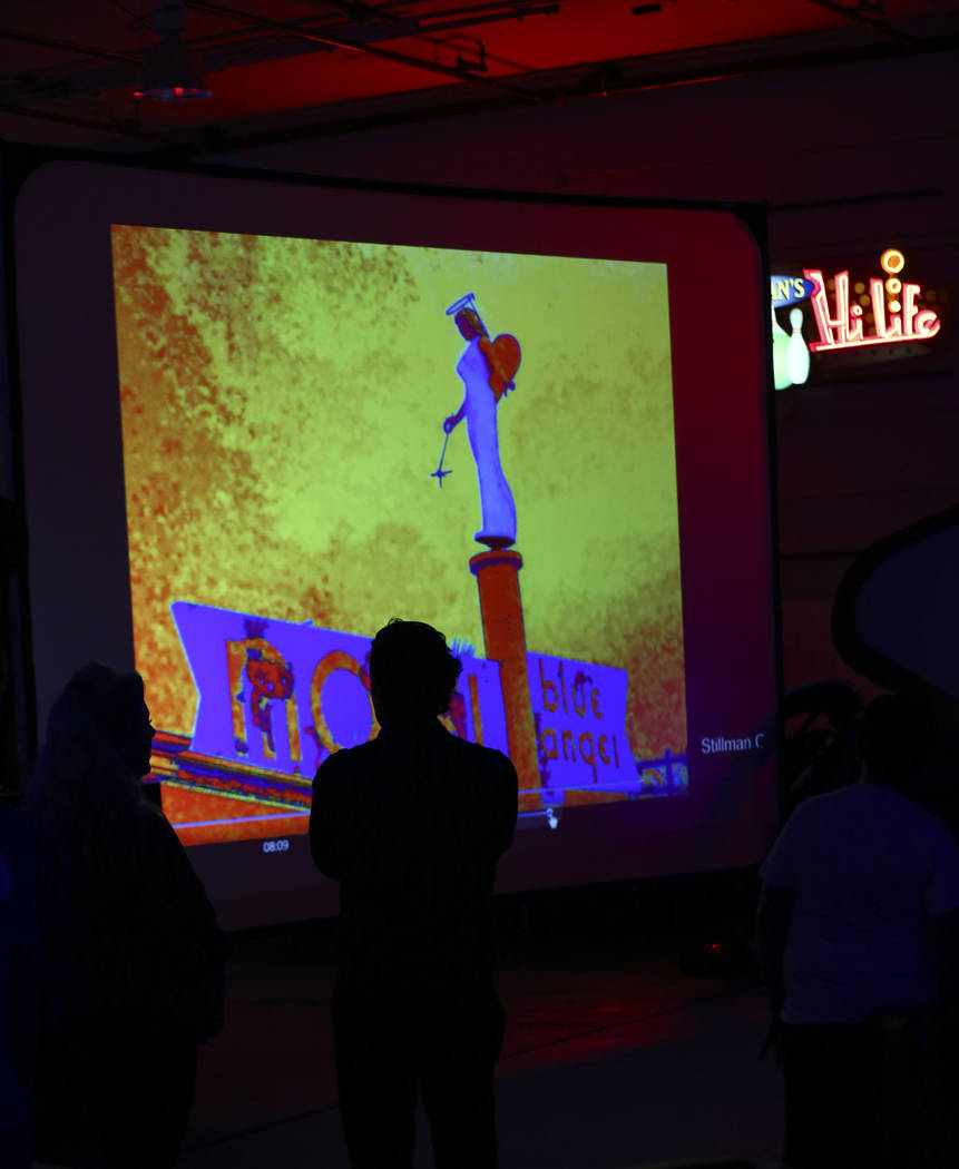 Visitors look at artwork and photos of the Blue Angel statue, designed by Betty Willis, at the Neon Museum's Ne10 Studio in Las Vegas on Thursday, May 24, 2018. The statue came down from its perch ...